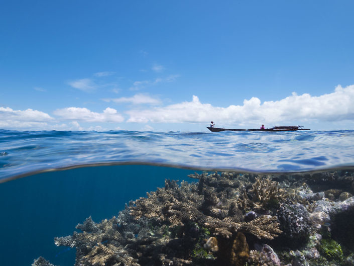 Split shot image of a local boat with a coral reef below.